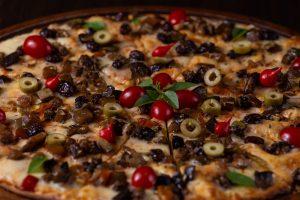 pizza z oliwkami, pomidorami i bazylią